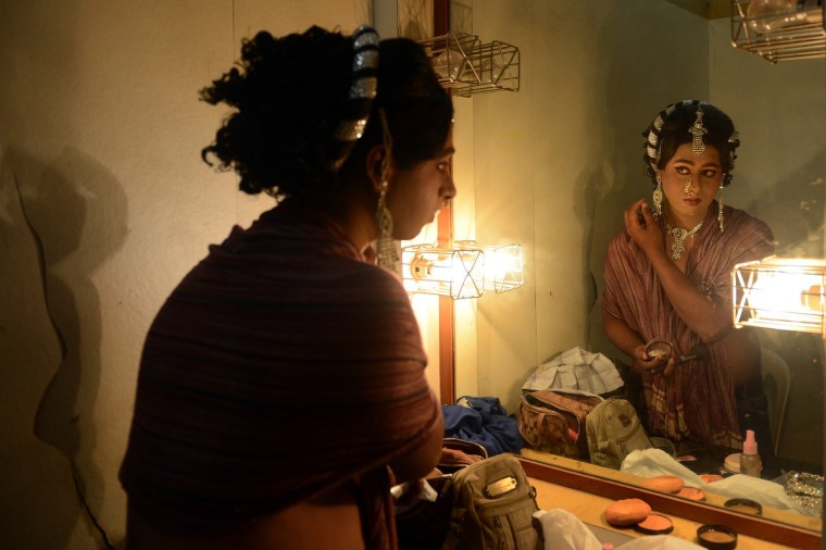 An Indian man, dressed as a female, gets ready for the 'Lavani' performance in Mumbai. Lavani is a genre of music, a combination of traditional song and dance which is particularly performed to the beat of the Dholki, a percussion instrument. The dance, noted for its powerful rhythm and erotic sentiment, is performed by female performers wearing nine-yard long saris. (Punit Paranjpe/Getty Images)