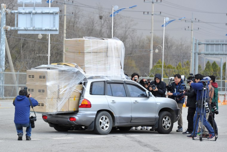 Members of South Korea's media surround a car filled with workers returning from the Kaesong Industrial Park with boxes loaded on top of their car at a gate of the inter-Korean transit office in the border city of Paju. North Korean workers failed to show on April 9 at the Kaesong joint industrial zone, a day after Pyongyang said it was withdrawing labour and suspending operations at the Seoul-funded complex. (Kim Jae-Hwan/Getty Images)
