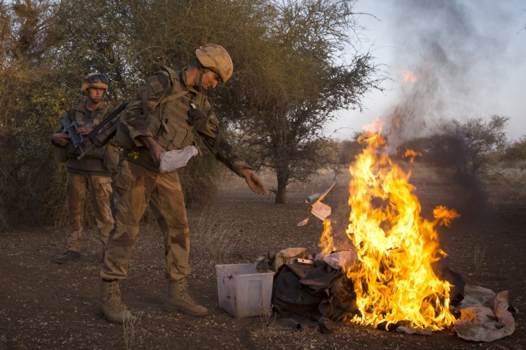 """French soldiers from the 92nd Regiment Infantry burn items allegedly belonging to Mujao forces during a military operation some 105 kilometers North of Gao. A French force of 1,000 soldiers in a major offensive has swept a valley thought to be a logistics base for Al-Qaeda-linked Islamists near the Malian city of Gao. Operation Gustav, one of France's largest actions since its intervention against insurgents in January, will involve dozens of tanks, helicopters, drones and airplanes, said General Bernard Barrera, commander of the French land forces in Mali. France is to start withdrawing its 4,000 troops from Mali at the end of April, and plans to leave a """"support force"""" of 1,000 soldiers after elections promised for July. (Joel Saget/Getty Images)"""