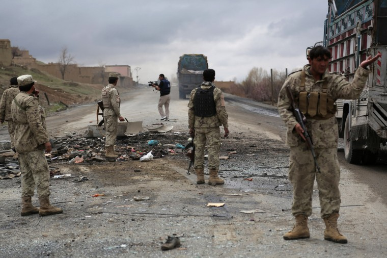 """Afghanistan security forces stand guard at the site of a roadside bomb blast in Saidabad district of Wardak province. A roadside bomb exploded under an Afghan bus southwest of Kabul on Monday, killing nine people and wounding at least 22 others in an attack blamed on Taliban militants, officials said. The bus bombing in the flashpoint province of Wardak came as Afghanistan endures a bloody few days at a time of year that often sees a surge in violence as the cold winter recedes and the so-called """"fighting season"""" begins. (Rahmatullah Alizad/Getty Images)"""
