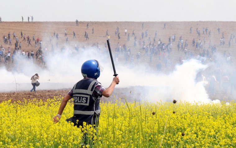 Turkish riot policemen and soldiers clash with protestors in a field during a demonstration at Dicle University, in Diyarbakir. Leftist Kurdish students protest after a clashing between left and right-wing groups inside Dicle University. (Mehmet Engin/Getty Images)