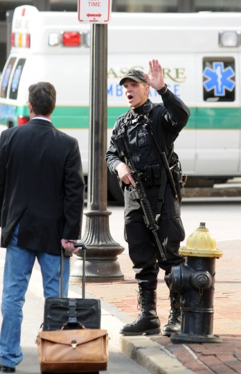 A Boston police officer yells at a pedestrian to evacuate the area after explosions rocked the finish area of the Boston Marathon on April 15, 2013 in Boston, Massachusetts. At least two people were killed and 22 wounded when two explosions struck near the finish line of the Boston Marathon, sparking scenes of panic, police said. The streets were littered with debris and blood and paramedics raced off with stretchers as police locked down the area, witness said. TV footage showed an explosion sending up a white plume of smoke along the sidelines of the race. (John Mottern/AFP/Getty Images)