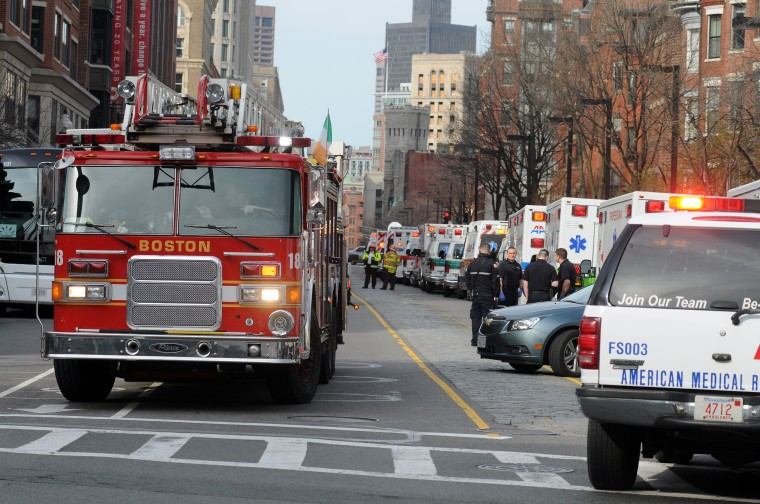 A long line of ambulances wait in a staging area after explosions rocked the finish area of the Boston Marathon on April 15, 2013 in Boston, Massachusetts. At least two people were killed and 22 wounded when two explosions struck near the finish line of the Boston Marathon, sparking scenes of panic, police said. The streets were littered with debris and blood and paramedics raced off with stretchers as police locked down the area, witness said. TV footage showed an explosion sending up a white plume of smoke along the sidelines of the race. (John Mottern/AFP/Getty Images)