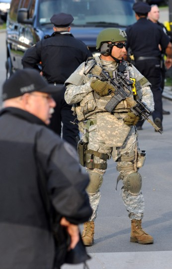 A member of the Boston Police S.W.A.T. team stands guard at a staging area located at the Boston Common at the Boston Marathon where several explosions rocked the event April 15, 2013 in Boston, Massachusetts. At least two people were killed and 22 wounded when two explosions struck near the finish line of the Boston Marathon, sparking scenes of panic, police said. The streets were littered with debris and blood and paramedics raced off with stretchers as police locked down the area, witness said. TV footage showed an explosion sending up a white plume of smoke along the sidelines of the race. (John Mottern/Getty Images)