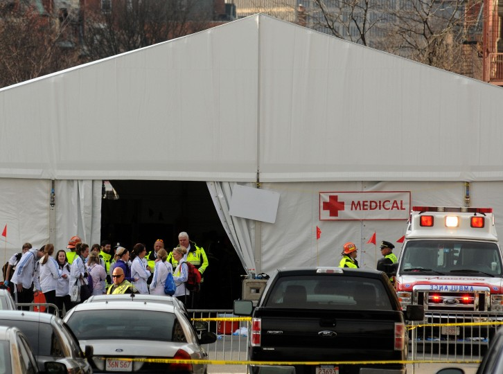 Staff stand outside a medical tent near the finish line of the Boston Marathon where several explosions rocked the event April 15, 2013 in Boston, Massachusetts. Two explosions struck one of America's top sporting events, killing at least two and wounding dozens as the Boston Marathon erupted in a maelstrom of blood, screams, smoke and panic. (John Mottern/AFP/Getty Images)