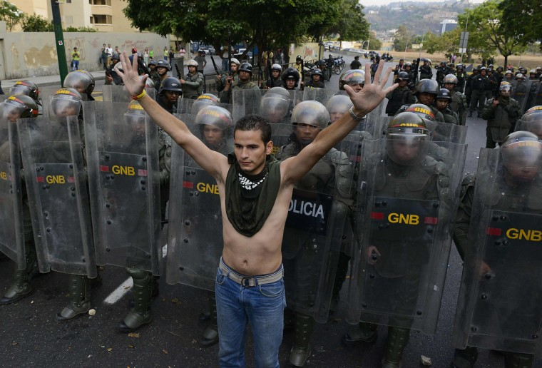A supporter of Venezuelan opposition presidential candidate Henrique Capriles protests in front of riot police in Caracas. Venezuela's acting President Nicolas Maduro was proclaimed the winner of an election to succeed late leader Hugo Chavez here Monday triggering protests as the opposition demanded a recount. (Leo Ramirez/Getty Images)