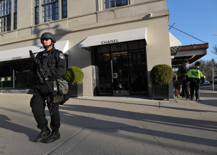 """A heavily armed Boston police officer stands guard in front of the Taj Hotel April 16, 2013 in Boston, Massachusetts, in the aftermath of two explosions that struck near the finish line of the Boston Marathon April 15. A massive probe was underway Tuesday after two bombs struck the Boston Marathon, killing at least three and wounding more than 100. Monday's blasts near the finishing line raised fears of a terrorist attack more than a decade after nearly 3,000 people were killed in suicide airliner strikes on New York, Washington and Pennsylvania on September 11, 2001. US President Barack Obama went on national television to warn against """"jumping to conclusions"""" but a senior White House official, speaking on condition of anonymity, said such an attack was """"clearly an act of terror."""" (Stan Honda/Getty Images)"""