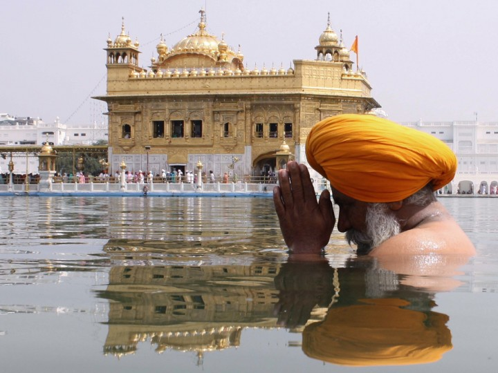 An Indian Sikh devotee takes a holy dip in the sarover (water tank) at the Golden Temple in Amritsar. (Narinder Nanu/Getty Images)