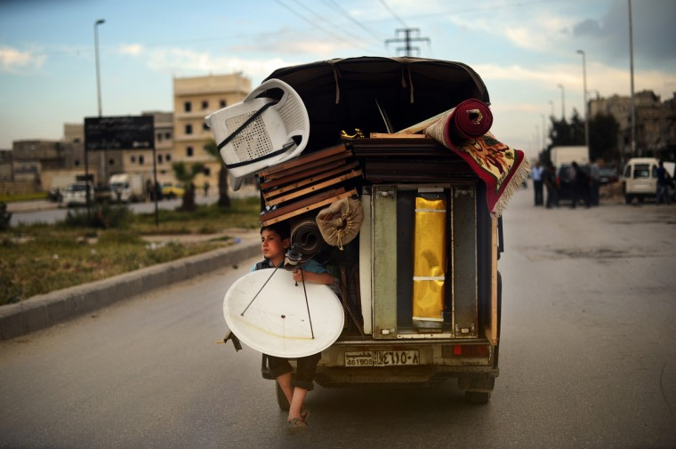 A Syrian boy holds a satellite antenna as he travels on the back of a truck in the northern Syrian city of Aleppo. In all, some 1.3 million people have so far fled Syria to neighboring countries since the beginning of the conflict, which has cost well over 70,000 lives. (Dimitar Dilkoff/Getty Images)