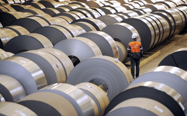"""An employee looks at coils of steel treated by galvanization are stored in the world's largest steel maker ArcelorMittal's """"cold factory"""" of the northeastern France plant of Florange. Usibor steel (weight savings and improved crashworthiness) are producted in the cold factory. (Jean-Christophe Verhaegen/Getty Images)"""