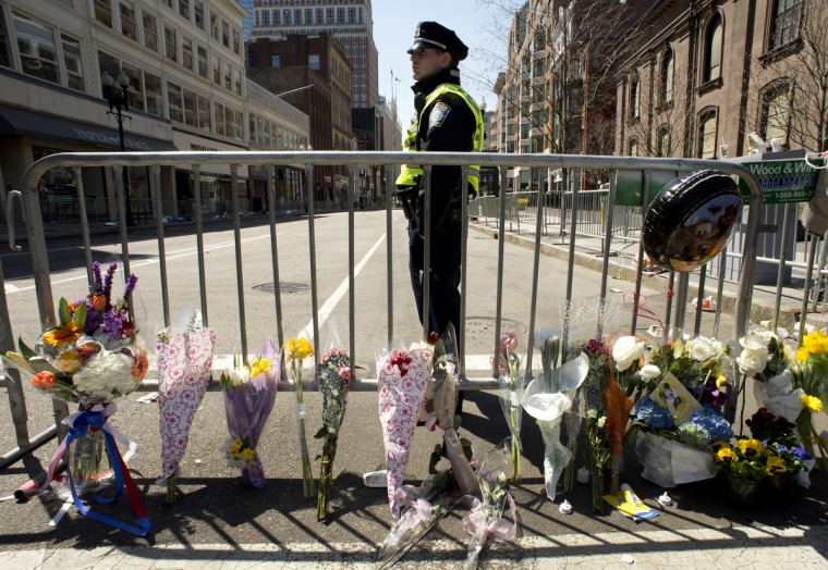A Boston police officer stands guard at a memorial site at Boylston and Arlington streets along the course of the Boston Marathon on April 16, 2013, a few blocks from where two explosions struck near the finish line of the Boston Marathon on April 15. (Don Emmert/Getty Images)