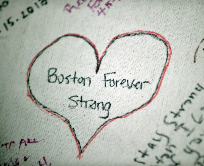 """A message written on a banner seen during a vigil on the Boston Common on April 16, 2013 in Boston, in the aftermath of two explosions that struck near the finish line of the Boston Marathon on April 15. Investigators said the range of suspects and motives in the grisly Boston bombings remained """"wide open"""" as experts assessed remnants of the crude devices designed to inflict maximum suffering. (Stan Honda/AFP/Getty Images)"""