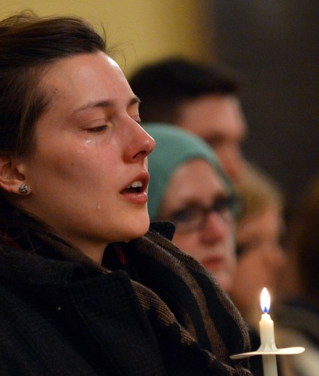 A woman cries during a candlelight interfaith service at Arlington Street Church April 16, 2013 in Boston, Massachusetts, in the aftermath of two explosions that struck near the finish line of the Boston Marathon April 15. (Stan Honda/AFP/Getty Images)