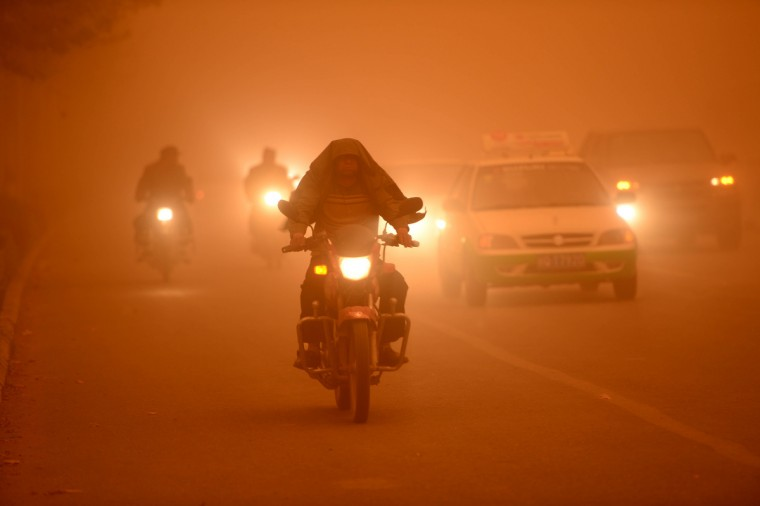 Motorists drive with their lights during a heavy sandstorm in Yecheng county, northwest China's Xinjiang Uygur Autonomous Region. The sandstorm affected several cities including Kashi, Hetian and Kezhou. (Getty Images)