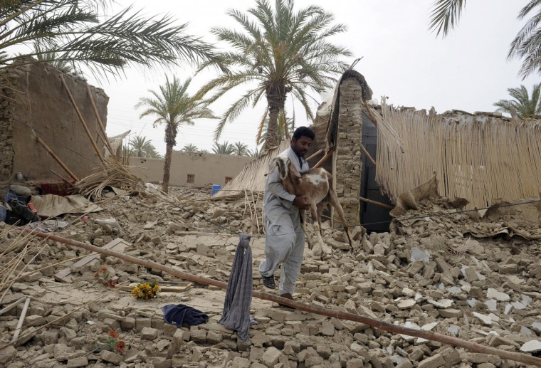 A Pakistani earthquake survivor carries a goat among the rubble of collapsed mud houses in the Mashkail area of southwestern Baluchistan province. Pakistani troops scrambled to aid the remote victims of an earthquake centred in nearby Iran, as the United States offered assistance and a strong aftershock jolted the region. The epicentre of the 7.8 magnitude quake on April 16, lay in southeast Iran but all 40 deaths reported so far have been across the border in Pakistan's dirt-poor province of Baluchistan, where hundreds of mud-built homes suffered damage. (Banaras Khan/Getty Images)