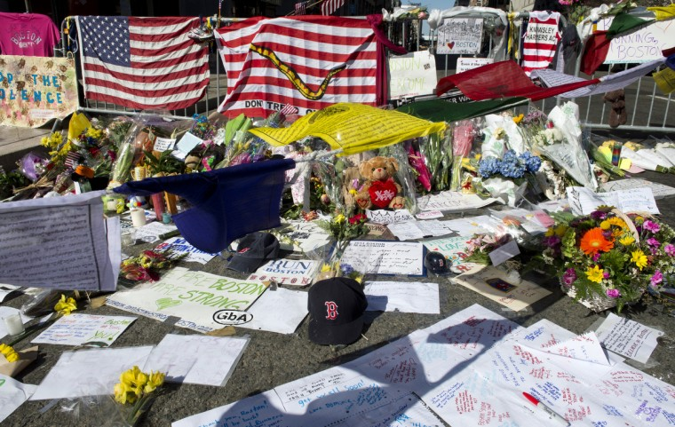 A Boston Red Sox cap is part of a makeshift memorial on the Boston Marathon route April 18, 2013 in Boston. (Don Emmert/Getty Images)