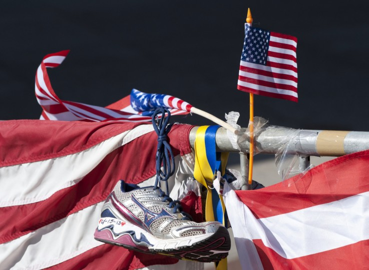 A running shoe and US flag are part of a memorial on the Boston Marathon route on April 18, 2013 in Boston. Three people died when two bombs went off near the finish line during the April 15 running of the 2013 Boston Marathon. (Don Emmert/Getty Images)