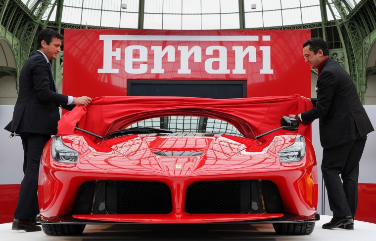 Employees of the Italian car maker Ferrari present the LaFerrari car in Paris. The new sports car is limited to 499 copies. (Pierre Andrieu/Getty Images)