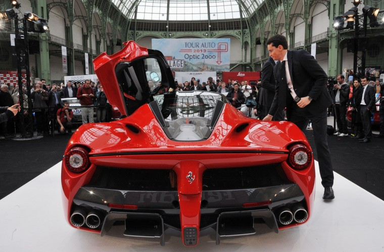 Employees of the Italian car maker Ferrari present the LaFerrari car. The production of the new sports car is limited to 499 copies. (Pierre Andrieu/Getty Images)