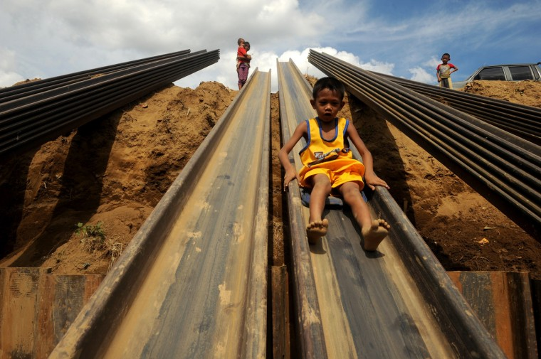 Children play on a metal beam in Manila. The Philippines has failed to make headway in cutting rampant poverty, with more than one in four citizens deemed poor despite the country's economic growth, according to census figures released Tuesday. The July 2012 poverty rate of 27.9 percent is practically unchanged from 2006 and 2009 data, according to the National Statistical Coordination Board. (Noel Celis/Getty Images)