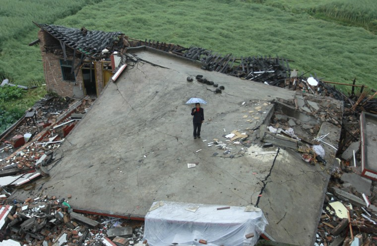 A woman stands on a collapsed house in Longmen township, one of the seriously-damaged towns in disaster-hit Yaan, southwest China's Sichuan province. Clogged roads, debris and landslides impeded rescuers on April 22 as they battled to find survivors of a powerful earthquake in mountainous southwest China that has left at least 192 dead. (Getty Images)