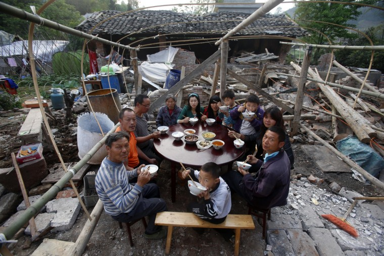 Local residents have a family gathering meal outside their damaged home after the earthquake in Yaan, southwest China's Sichuan province. Tens of thousands of homeless survivors of China's devastating quake are living in makeshift tents or on the streets, facing shortages of food and supplies as well as an uncertain future. (Getty Images)