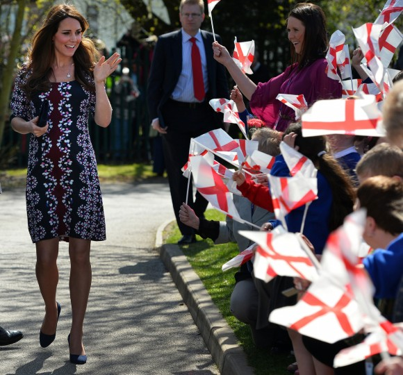 Britain's Catherine, Duchess of Cambridge (L) waves at children waving English flags as she arrives on her visit to The Willows Primary School, Wythenshawe, Manchester, northwest England on April 23, 2013 to launch a new school counselling programme. The duchess of Cambridge met staff and volunteers, teachers and parents at the school as she launched the program, which is a partnership between the Royal Foundation, Comic Relief, Place2Be and Action on Addiction. (Paul Ellis/Getty Images)