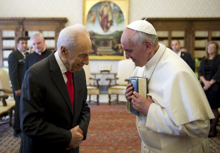 Pope Francis (R) and Israeli President Shimon Peres exchange gifts during a private audience in the pontiff's library at the Vatican. Israeli president and Nobel peace laureate Shimon Peres invited Pope Francis on an official state visit to Israel after a meeting in the Vatican on Tuesday. (Ettore Ferrari/Getty Images)