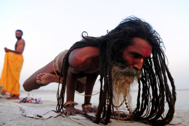 An Indian Hindu Sadhu (holy man) performs yoga on the banks of the Sangam in Allahabad. Yoga, which means union in Sanskrit, is a family of ancient spiritual practices and also a school of spiritual thought from the Asian subcontinent, where it remains a vibrant living tradition and is seen as a meaning of enlightenment. (Sanjay Kanojia/Getty Images)