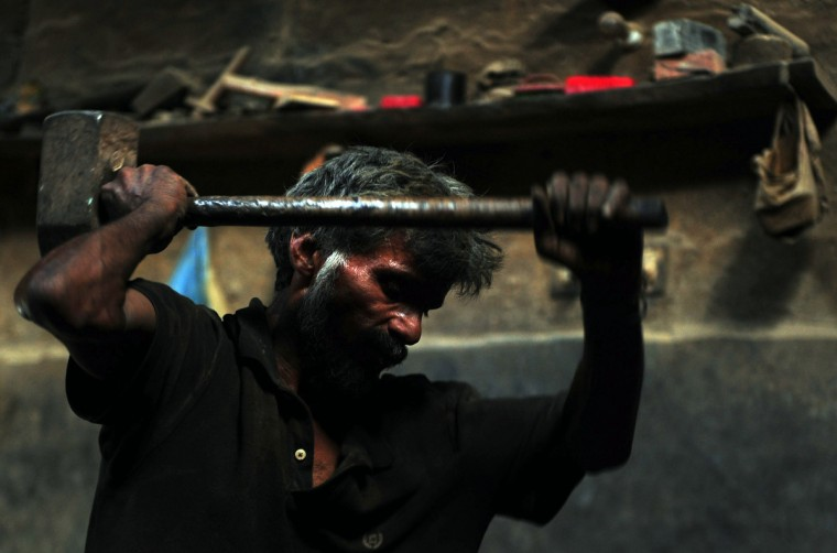 A Pakistani labourer uses a hamer as he works at an iron factory in Karachi, on the eve of International Labour Day. Pakistan has a workforce of around 56 million people among a population of 179 million, according to Pakistan's official figures compiled by the Federal Bureau of Statistics. (Asif Hassan/Getty Images)