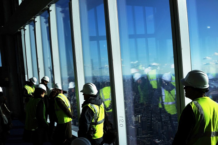 Visitors stand near the windows. When the space opens in 2015, it will include a pre-show theater, multiple spaces that allow for panoramas of the New York City region and numerous dining options. (Spencer Platt/Getty Images)