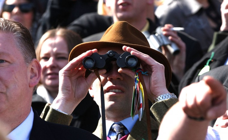 Racegoers watch the Grand National Steeplechase with binoculars at Aintree on April 6, 2013 in Liverpool, England. Millions of pounds are wagered on the 40 runners taking part in the race. (Danny E. Martindale/Getty Images)