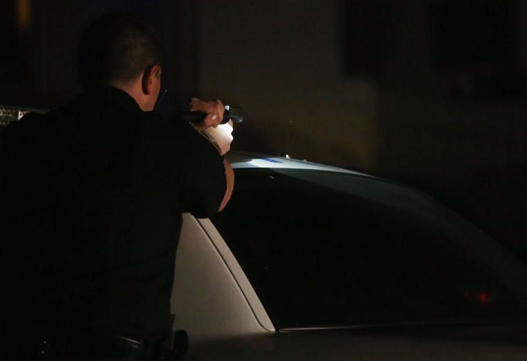 A police officer with gun drawn and flashlight searches for a suspect on April 19, 2013 in Watertown, Massachusetts. Earlier, a Massachusetts Institute of Technology campus police officer was shot and killed late Thursday night at the school's campus in Cambridge. A short time later, police reported exchanging gunfire with alleged carjackers in Watertown, a city near Cambridge. According to reports, one suspect has been killed during a car chase and the police are seeking another - believed to be the same person (known as Suspect Two) wanted in connection with the deadly bombing at the Boston Marathon earlier this week. Police have confirmed that the dead assailant is Suspect One from the recently released marathon bombing photographs. (Mario Tama/Getty Images)