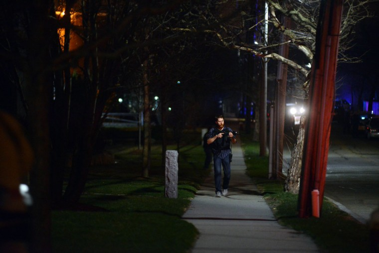 Police descend on School and Walnut Street chasing possible suspects on April 19, 2013 in Watertown, Massachusetts. Earlier, a Massachusetts Institute of Technology campus police officer was shot and killed at the school's campus in Cambridge. A short time later, police reported exchanging gunfire with alleged carjackers in Watertown, a city near Cambridge. According to reports, one suspect has been killed during a car chase and the police are seeking another - believed to be the same person (known as Suspect Two) wanted in connection with the deadly bombing at the Boston Marathon earlier this week. Police have confirmed that the dead assailant is Suspect One from the recently released marathon bombing photographs. (Darren McCollester/Getty Images)