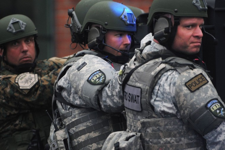 Metro SWAT members hang off the back of a truck as they prepare to search the School and Walnut Street neighborhood for one remaining suspect on April 19, 2013 in Watertown, Massachusetts. Earlier, a Massachusetts Institute of Technology campus police officer was shot and killed at the school's campus in Cambridge. A short time later, police reported exchanging gunfire with alleged carjackers in Watertown, a city near Cambridge. According to reports, one suspect has been killed during a car chase and the police are seeking another - believed to be the same person (known as Suspect Two) wanted in connection with the deadly bombing at the Boston Marathon earlier this week. Police have confirmed that the dead assailant is Suspect One from the recently released marathon bombing photographs. (Darren McCollester/Getty Images)