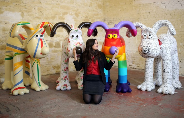 Fundraising manager Lauren Vincent poses with four Gromit sculptures, out of around 70 which have been painted by celebrity artists, (L-R) Sir Paul Smith, Cath Kidston, Richard Williams and Simon Tofield, before they are placed around the city for public view as part of charity initiative arts trail in Bristol, England. After being displayed to the public from July 1, the sculptures will be eventually auctioned off to raise funds for the Bristol Children's Hospital charity, Wallace & Gromit's Grand Appeal. (Matt Cardy/Getty Images)