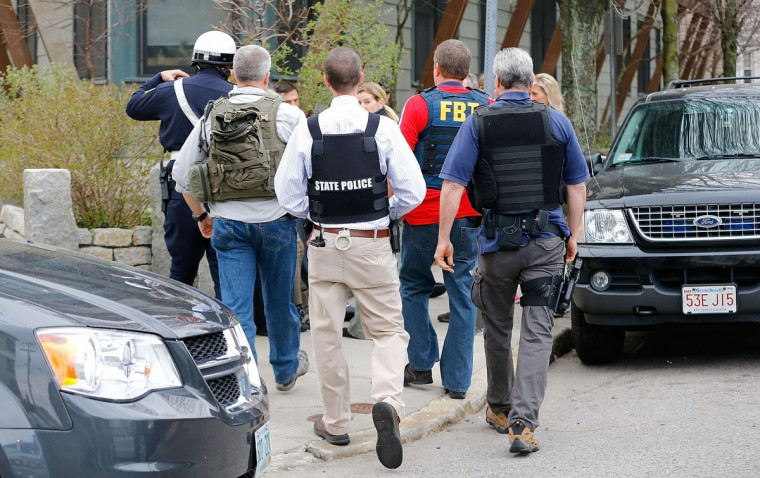 Members of the FBI, State Police, Boston Police, Cambridge Police, and other law enforcement agencies, survey the perimeter on April 19, 2013 in Cambridge, Massachusetts near the home of a suspect in the Boston marathon bombings. Earlier, a Massachusetts Institute of Technology campus police officer was shot and killed late Thursday night at the school's campus in Cambridge. A short time later, police reported exchanging gunfire with alleged carjackers in Watertown, a city near Cambridge. According to reports, one suspect has been killed during a car chase and the police are seeking another - believed to be the same person (known as Suspect Two) wanted in connection with the deadly bombing at the Boston Marathon earlier this week. Police have confirmed that the dead assailant is Suspect One from the recently released marathon bombing photographs. (Jared Wickerham/Getty Images)