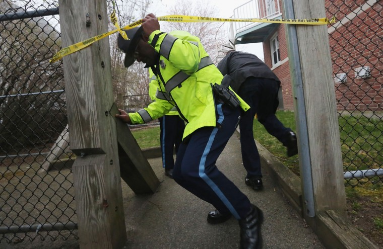 Police search for one remaining suspect at an apartment building where a resident reported finding drops of blood on April 19, 2013 in Watertown, Massachusetts. Earlier, a Massachusetts Institute of Technology campus police officer was shot and killed at the school's campus in Cambridge. A short time later, police reported exchanging gunfire with alleged carjackers in Watertown, a city near Cambridge. According to reports, one suspect has been killed during a car chase and the police are seeking another - believed to be the same person (known as Suspect Two) wanted in connection with the deadly bombing at the Boston Marathon earlier this week. Police have confirmed that the dead assailant is Suspect One from the recently released marathon bombing photographs. (Mario Tama/Getty Images)