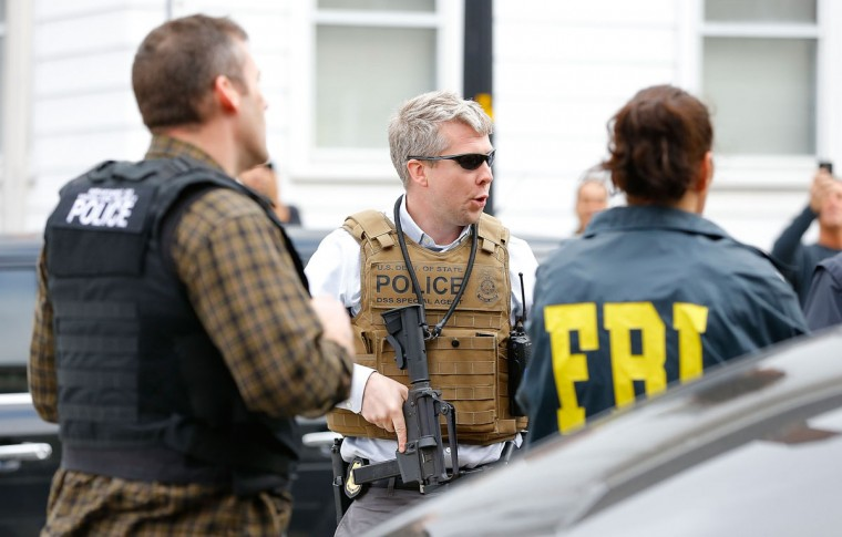 Members of the FBI, State Police, Boston Police, Cambridge Police, and other law enforcement agencies, survey the perimeter near the home of a suspect in the Boston marathon bombings, on April 19, 2013 in Cambridge, Massachusetts. A Massachusetts Institute of Technology (MIT) campus police officer was shot and killed late Thursday night at the school's campus in Cambridge. A short time later, police reported exchanging gunfire with alleged carjackers in Watertown, a city near Cambridge. One suspect has been killed during the car chase and police are seeking another, believed to be the same person (known as Suspect Two) wanted in connection with the deadly bombing at the Boston Marathon earlier this week. Police have confirmed that the dead assailant is Suspect One from the recently released marathon bombing photographs. (Jared Wickerham/Getty Images)