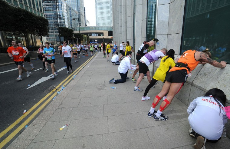 Runners try and stretch out their fatigue. (Charlie Crowhurst/Getty Images)
