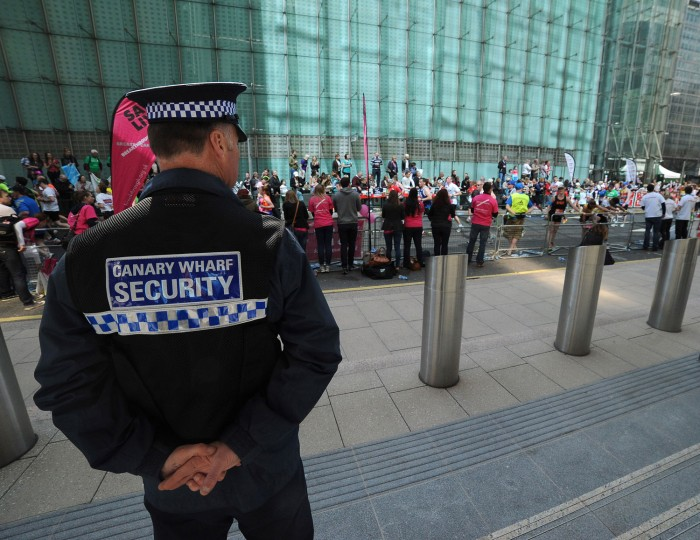 A Canary Wharf Security guard keeps an eye on the crowd. (Charlie Crowhurst/Getty Images)