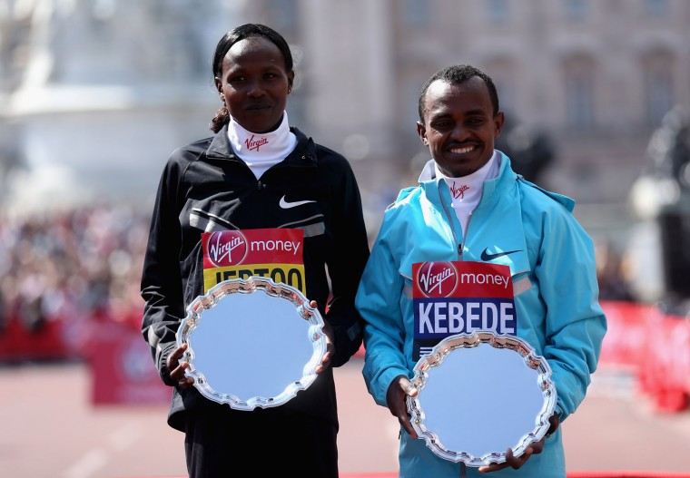 Men's elite race winner Tsegaye Kebede of Ethiopia (R) and women's elite race winner Priscah Jeptoo of Kenya (L) pose with their shields after winning their respective categories. (Getty Images)