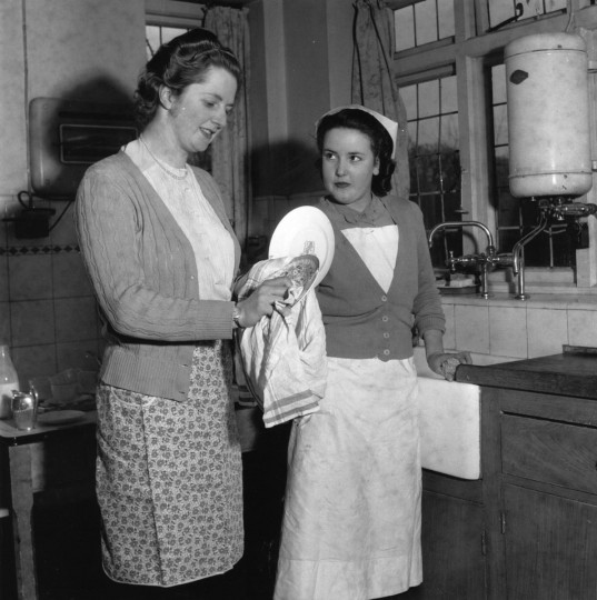 Conservative politician and future prime minister Margaret Hilda Thatcher, wiping dishes whilst a nurse looks on in this undated photo. (Chris Ware/Getty Images)