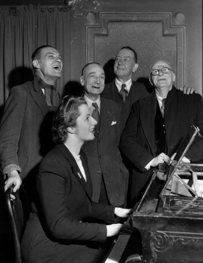 Circa 1950: Conservative candidate Margaret Roberts accompanies four voters on the piano in a sing-song after a brief political argument in the bar of The Bull Inn, Dartford. (Keystone/Getty Images)