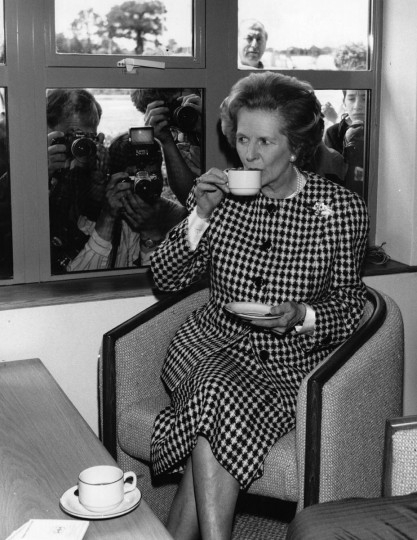 British Conservative Prime Minister, Margaret Thatcher, enjoys a cup of tea at the opening of the South Mimms Motorway service area, watched by the press June 6, 1987. (Keystone/Getty Images)