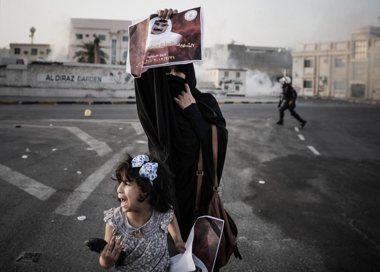 A Bahraini woman, standing with her daughter, holds up a picture of Abd Al-Ghani Al-Rayes during clashes following his funeral procession in the village of Diraz, west of Manama on April 1, 2013. Al-Rayes, who was 66-years old, died in front of a police station following what medics presume was a heart-attack, as he was trying to find out what happened to his arrested son, family said. (Mohammed Al-Shaikh/AFP/Getty Images)
