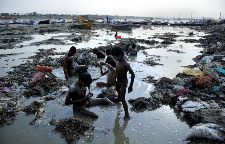 Indian men search for coins and gold in the polluted waters of the Ganga river at Sangam after the Kumbh Mela festival, in Allahabad on April 2, 2013. The two month long Kumbh Mela, celebrated every 12 years at the conjunction of two sacred rivers on the outskirts of the northern Indian city of Allahabad, drew massive crowds of devotees, ascetics and foreign tourists till its conclusion on March 10. (Sanjay Kanojia/AFP/Getty Images)