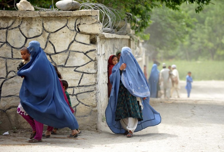 Afghan women scurry for cover as US soldiers patrol Kush Kunar district in Nangarhar on April 7, 2013. (Manjunath Kiran/AFP/Getty Images)