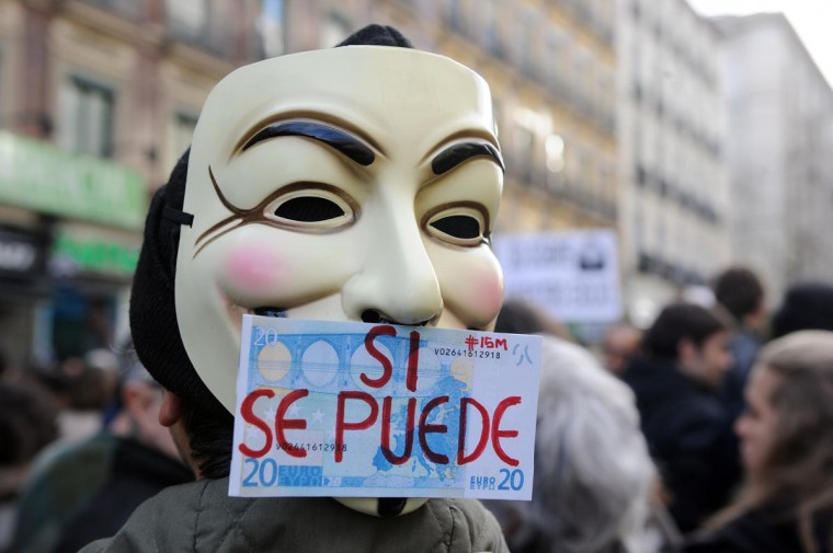 "A Spanish youth wears a Guy Fawkes mask with a written message on a 20 euros notes reading ""Yes we can"" as he takes part in protest against government's austerity measures forcing them to emigrate, in Madrid on April 7, 2013. (Dominique Faget/AFP/Getty Images)"