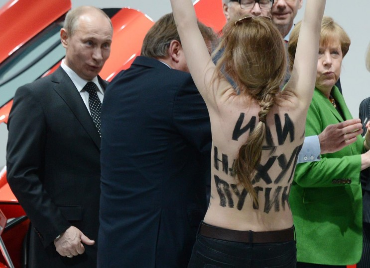 A topless demonstrator with a message on her back walks towards Russian President Vladimir Putin (L) and German Chancellor Angela Merkel (R) during their visit of the Hanover industrial Fair in Hanover, central Germany, on April 8, 213. (Jochen Lübke/AFP/Getty Images)